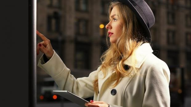 Young woman near digital screen in street at evening time